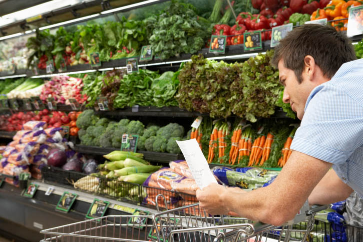 Man with shopping list in produce section of grocery store